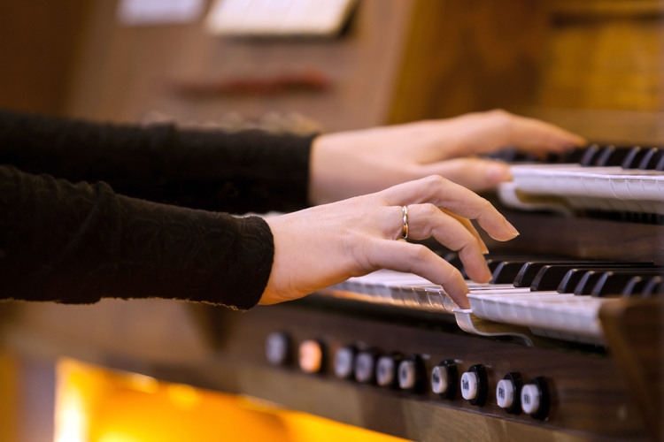 Hands of a woman playing the organ closeup